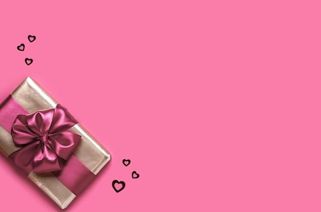 Подарок ко дню святого валентина на розовом фоне. концепция дня святого валентина. копия пространства. вид сверху.