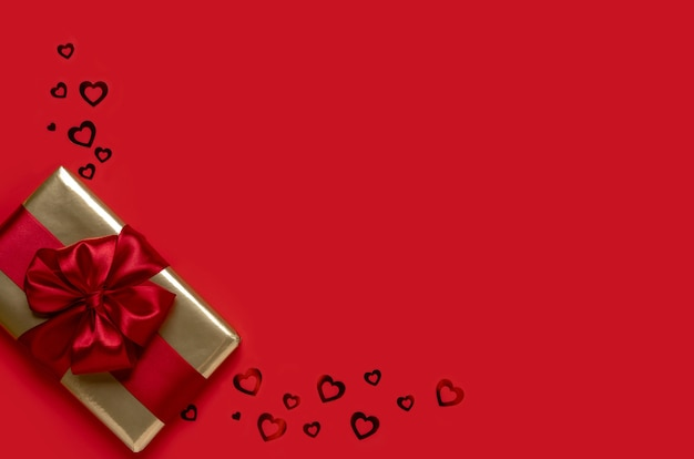 Подарок ко дню святого валентина на красном фоне. концепция дня святого валентина. копия пространства. вид сверху.