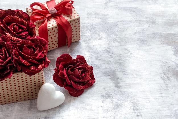 Подарок на день святого валентина с декоративными розами и белым сердцем на светлом фоне копией пространства.