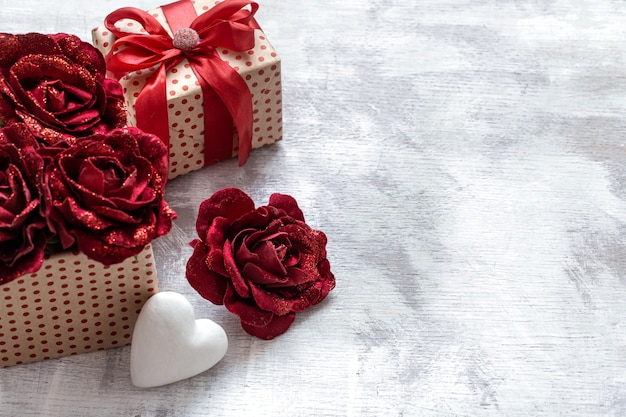 Valentine's day gift with decorative roses and white heart on light background copy space.
