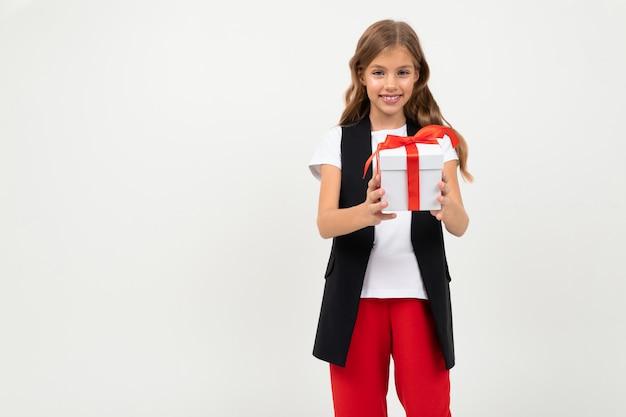 バレンタイン・デー 。 copyspaceと白の赤いリボンが付いているギフトを持つ少女