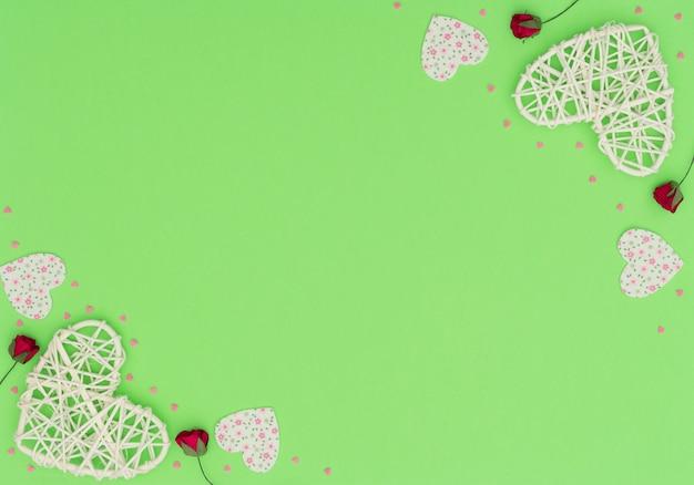 등나무와 펠트 하트, 빨간 장미와 작은 핑크 하트와 함께 발렌타인 데이 녹색.