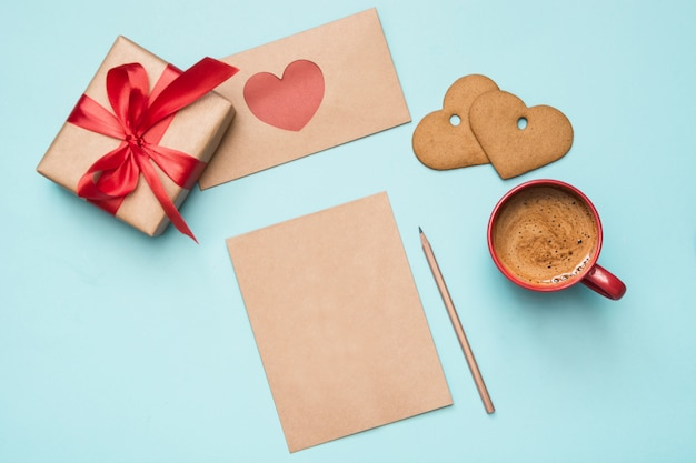 Valentine's day greeting card. blank for love letter with gift, red hearts, cookies on blue. top view.