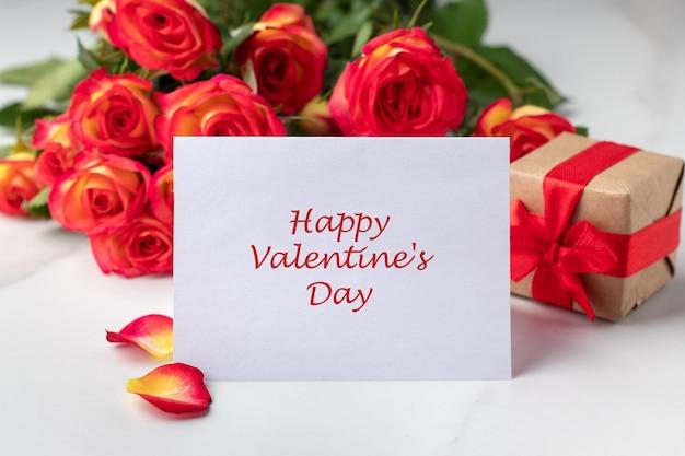 バレンタインデーのグリーティングカード、ギフトボックス、大理石のテーブルの上の美しいバラ。ロマンチックな休日