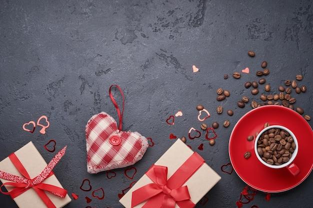Открытка ко дню святого валентина. подарочная коробка с красной лентой и чашка с зернами ароматного кофе, фигурки сердца