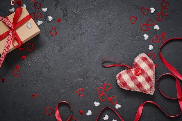 Открытка ко дню святого валентина. подарочная коробка с красной лентой и фигурками сердца