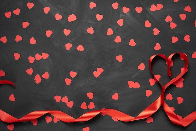 발렌타인 데이 인사말 카드. 심장 모양의 돌 배경에 빨간 리본. 복사 공간이있는 평면도