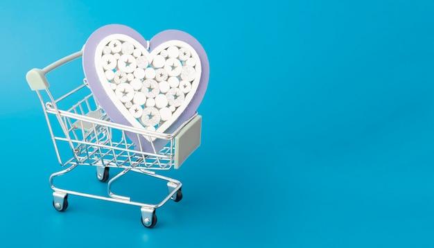 バレンタインデーのグリーティングカード、愛、ロマンスのコンセプト、コピースペースと青い背景の上のスーパーマーケットからのバスケットカートのギフトハート