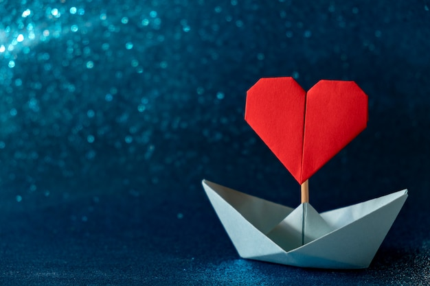 Поздравительная открытка дня святого валентина оригами лодка с флагом сердца на синем фоне блеска романтический, день святого валентина концепции с пространством для текста.