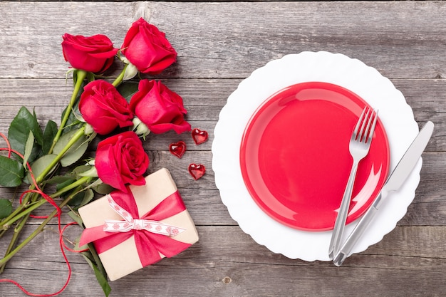 Valentine's day greeting card place setting with bouquet of roses, red hearts and silverware on gray wooden table. top view. copy space