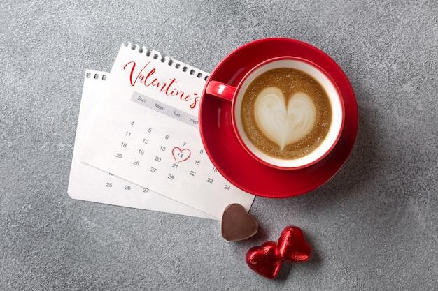 Поздравительная открытка дня святого валентина красная кофейная чашка и конфеты над календарем в феврале. вид сверху
