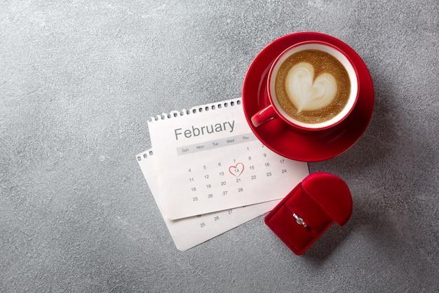 Поздравительная открытка дня святого валентина красная кофейная чашка, кольцо и подарочная коробка над календарем в феврале.