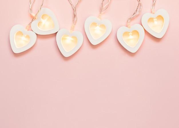 Открытка ко дню святого валентина. романтический розовый фон с сердечной гирляндой. день святого валентина или украшение свадебной вечеринки.