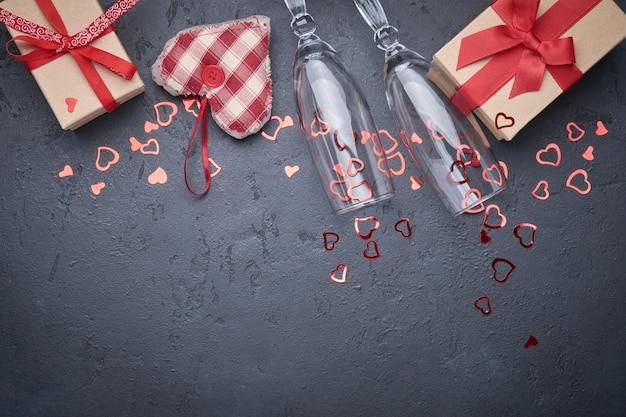 Открытка ко дню святого валентина. два бокала для шампанского, подарочная коробка с красной лентой и фигурки сердца