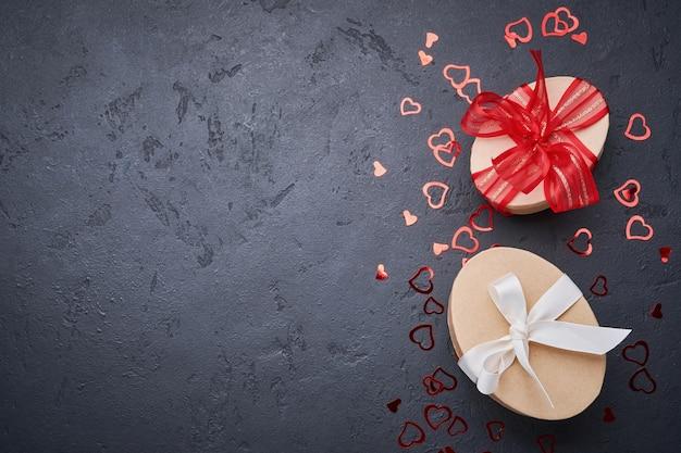 Открытка ко дню святого валентина. две подарочные коробки с красной лентой и фигурками сердца