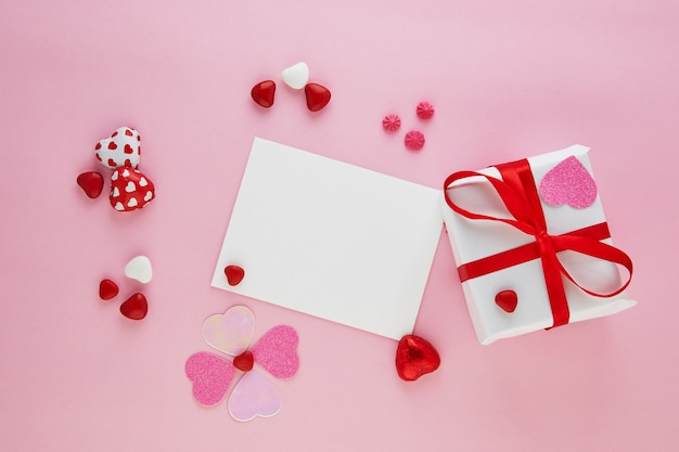 Поздравительная открытка дня святого валентина с конфетными сердцами и подарком с красной лентой на розовом столе. вид сверху с местом для поздравлений.
