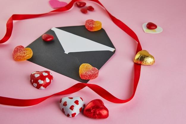 Поздравительная открытка дня святого валентина с сердечками конфеты и красной лентой на розовом столе. вид сверху с местом для поздравлений.