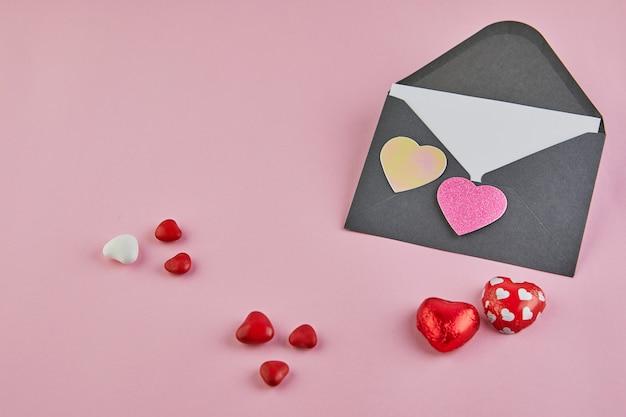 Открытка на день святого валентина с конфетными сердечками на розовой поверхности