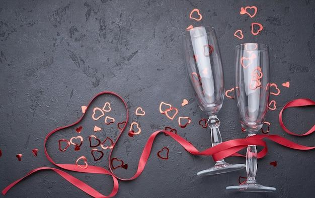 Открытка на день святого валентина с бокалами шампанского и конфетными сердечками