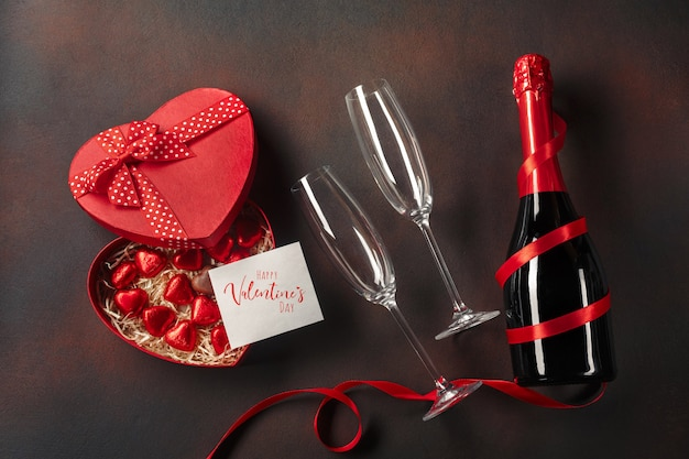 Valentine's day greeting card with champagne glasses and candy hearts on stone background.