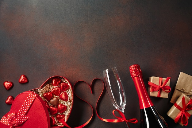 Valentine's day greeting card with champagne glasses and love gift box on stone background.