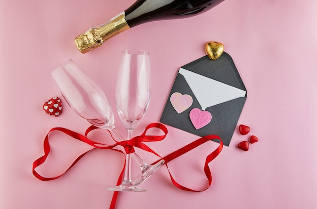 Valentine's day greeting card with glasses of champagne and candy hearts on pink. top view