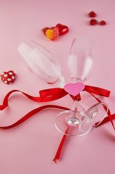 Поздравительная открытка дня святого валентина с бокалами шампанского и конфетными сердечками на розовом столе. вид сверху с местом для поздравлений. плоская планировка
