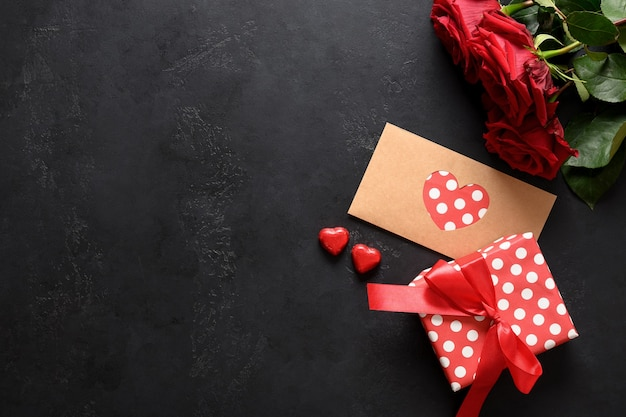 Valentine's day greeting card with love letter in decorative envelope, red roses and gift on black with copy space.