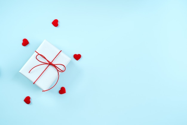 Valentine's day greeting handmade gift design concept - top view of wrapped gift box on bright blue background, flat lay overhead layout.