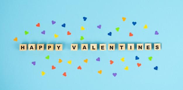 День святого валентина. счастливые валентины буквы на деревянных кубиках на синем фоне с сердечком. скопируйте пространство.