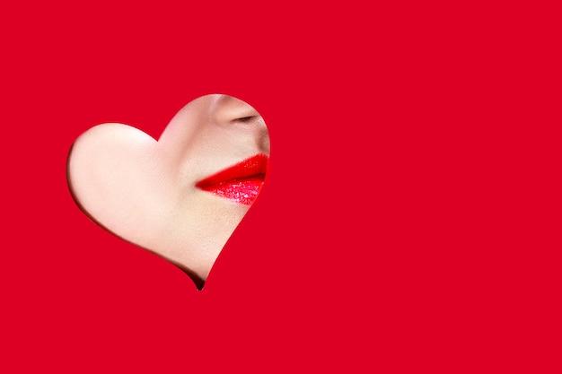 День святого валентина сердце и красивые женские пухлые губы на красном фоне. сладкий поцелуй. любовный макияж к дню вальнинца. форма сердца, как символ любви. копировать пространство