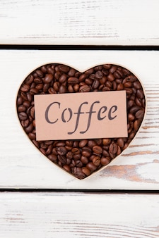 Valentine's day heart coffee grain. flat lay heart shaped coffee beans on white wood.
