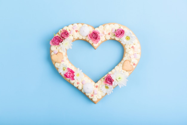 Valentine's day heart shaped cake with flowers as decoration.