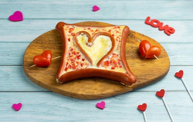 Завтрак для влюбленных в форме сердца с колбасой на день святого валентина. горизонтальная ориентация