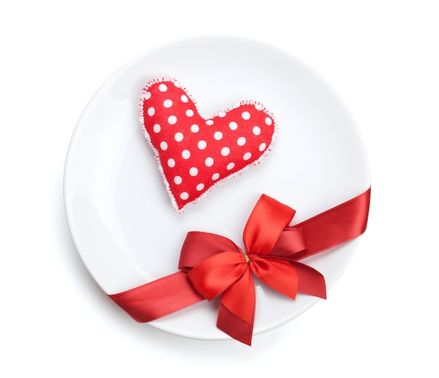Valentine's day heart shaped toy over plate with red bow. isolated on white background