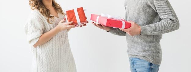 발렌타인 데이, 휴일 및 선물 개념입니다. 발렌타인 선물 흰색 배경에 고립 된 젊은 부부의 근접. 그의 여자 친구에게 선물을주는 행복한 남자.