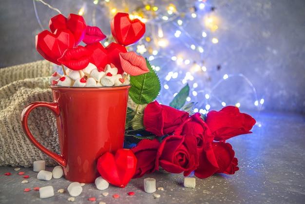 Праздник дня святого валентина с красной чашкой горячего шоколада и набором красных сердечек на палочках в чашке, с красными розами и эффектом боке