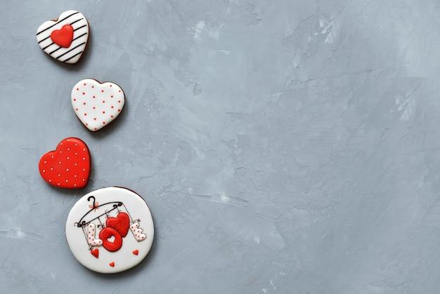 День святого валентина домашнее печенье на сером фоне, покрытое глазурью с красивым рисунком имбирных пряников.