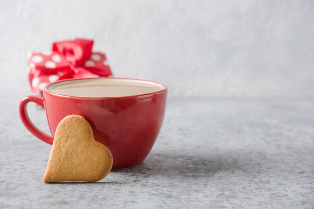 Valentine's day invitation. red cup of coffee with milk, gift and heart cookies on grey. close up.