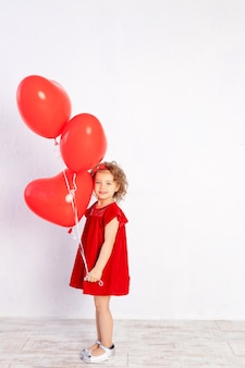 Valentine's day kids. little girl in red dress holding heart shaped balloons