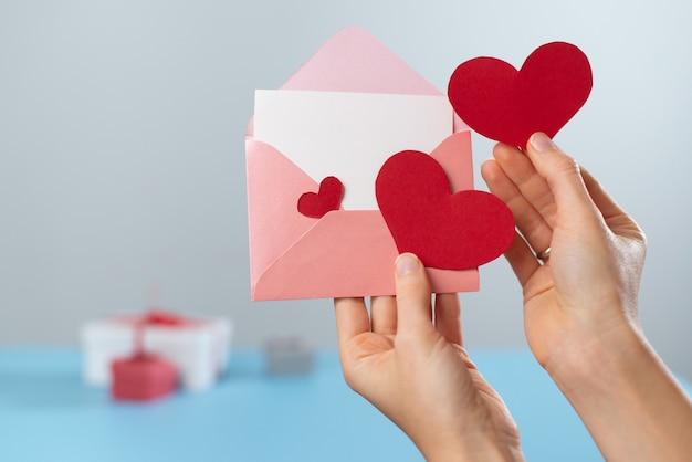Письмо дня святого валентина и конверт с копией пространства. предложение руки и сердца в руки. приглашение на свадьбу, признание в любви, поздравление с днем рождения.