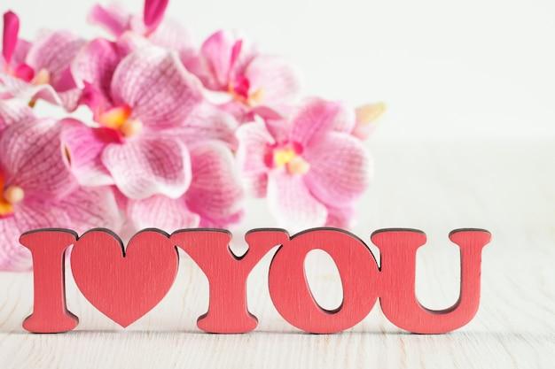 Письма ко дню святого валентина я люблю тебя и розовые цветы орхидеи на белом деревянном фоне