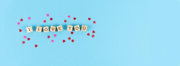 День святого валентина. письма я тебя люблю на деревянных кубиках на синем фоне с украшением сердца. скопируйте пространство.