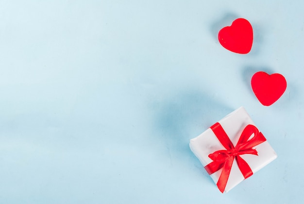 Valentine's day light blue  with gift box with red ribbon and red hearts. greeting card . top view copyspace