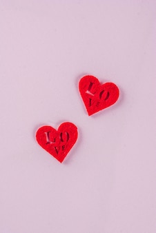 Valentine's day light pink background, greeting card concept, two red heart and two white hearts decoration, top view copy space
