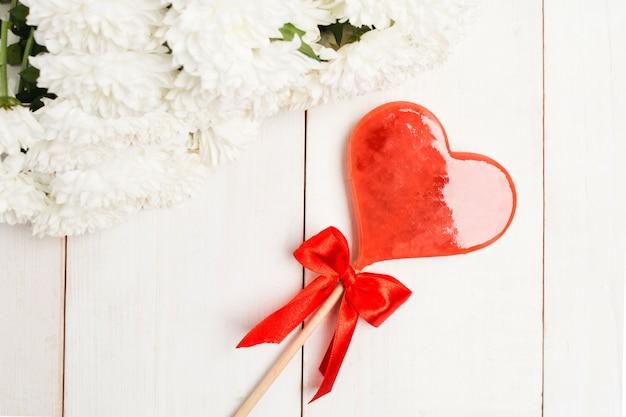 나무 테이블 위에 꽃과 하트 모양 발렌타인 롤리팝