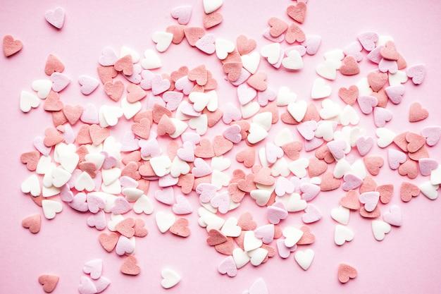 День святого валентина. концепция любви. день матери фон. сладкие сердечки на пастельном фоне, плоская планировка.