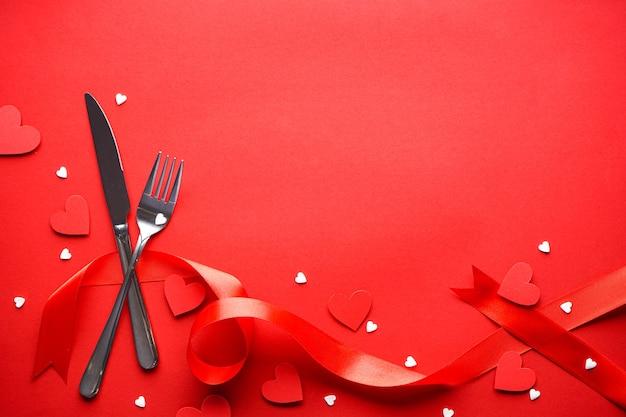 День святого валентина. концепция любви. день матери. сердечки со столовыми приборами и красной лентой на красном фоне, с пространством для текста, плоская планировка.