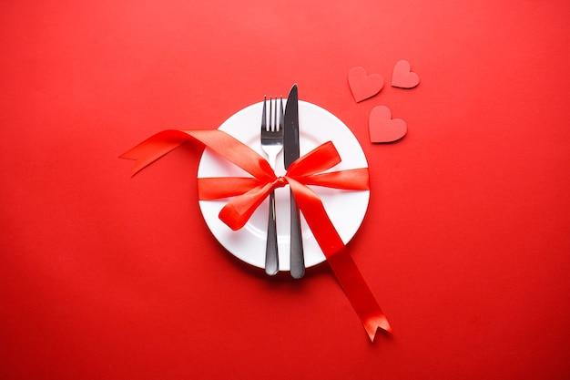 バレンタイン・デー。愛の概念。母の日。赤い背景に赤いリボンが付いた白いプレートにカトラリーが付いたハート、フラットレイ。