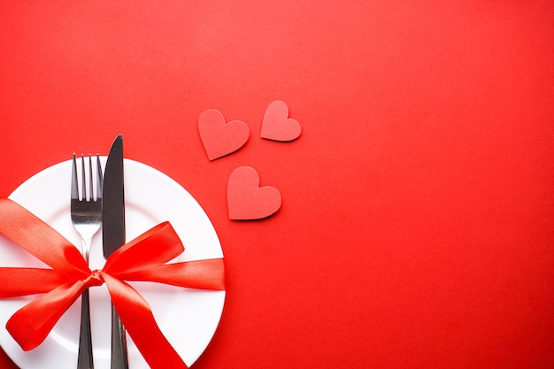 Valentine's day. love concept. mothers day. hearts with cutlery on a white plate with a red ribbon on a red background, flat lay, with space for text.